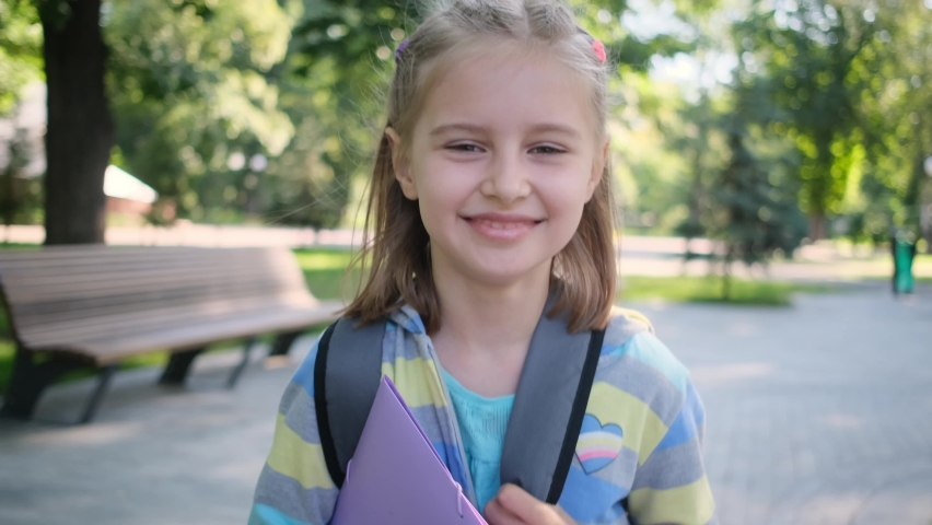 Schoolgirl with folder and backpack walking along park path | Shutterstock HD Video #1059122231