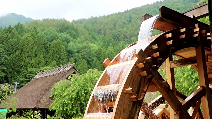 The mill wheel rotates under a stream of water at village with traditional thatched roofed houses, Japan. Royalty-Free Stock Footage #1059122447