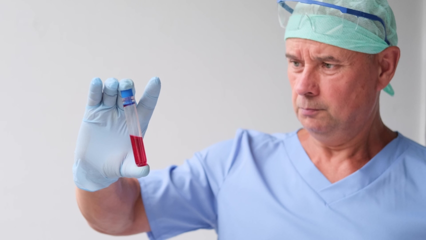 Male scientist, laboratory assistant, examines a blood sample in the laboratory, makes a dna test, examines a vaccine against COVID-19, the concept of innovation in modern science | Shutterstock HD Video #1059124322