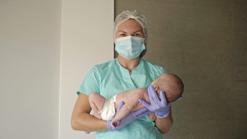 Female nurse holding a newborn baby in hospital.