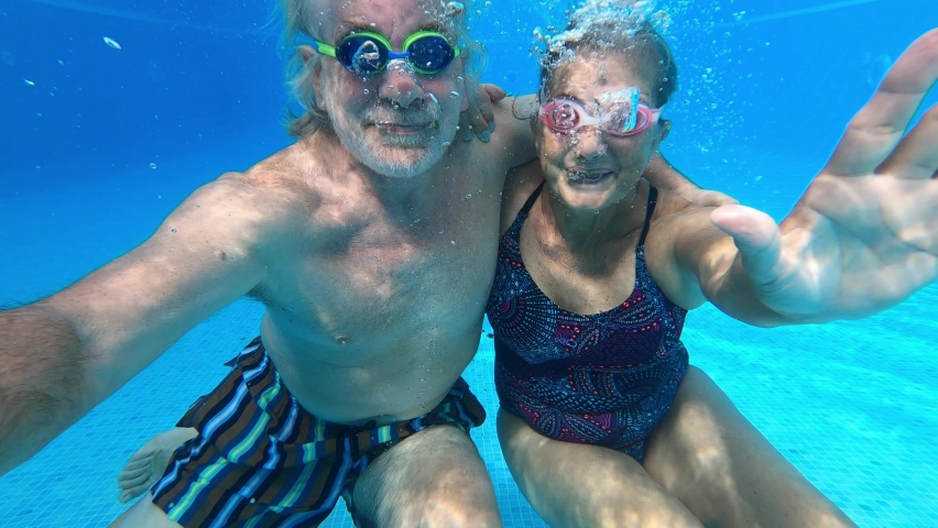 Couple of seniors enjoying summer and having fun together in the pool swimming and smiling looking at the camera - cheerful happy people in their vacations - portrait of two mature looking underwater | Shutterstock HD Video #1059126356