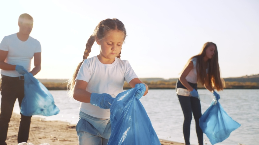 Kid collecting trash volunteer a teamwork. child group happy family on collects garbage plastic trash waste bottles. ecology environmental happy family teamwork volunteer awareness trash pollution