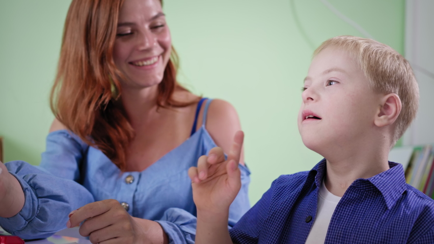 emotional boy with downs syndrome, kid rejoices in success gives five to the mother and applauds during doing homework at room Royalty-Free Stock Footage #1059127544