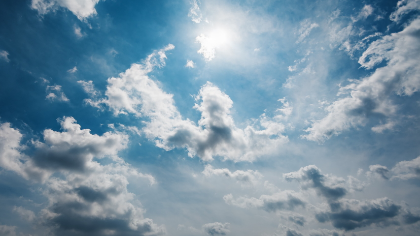 Heavenly beautiful timelapse of white fluffy clouds moving softly across bright blue sky and the sun shining glowingly and creating peaceful and dreamy atmosphere. Royalty-Free Stock Footage #1059129029