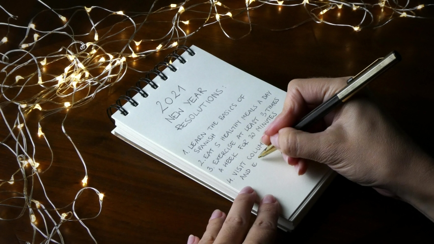 A woman writing a list of things to do or accomplish in 2021, making specific detailed resolutions for the new year, in a notebook in a festive setting with led lights on a dark wooden table. | Shutterstock HD Video #1059130142