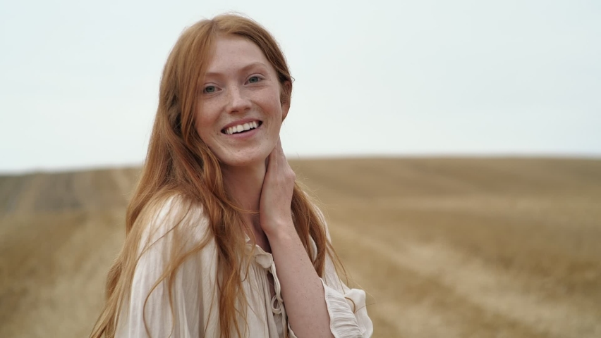 Natural Beauty Ginger Woman is running on golden Field happily, enjoying Nature. Amazing Woman touching her long Red Hair, smiling Charmingly. Looking Happy, feeling Liberty at Countryside. Emotions. Royalty-Free Stock Footage #1059133241