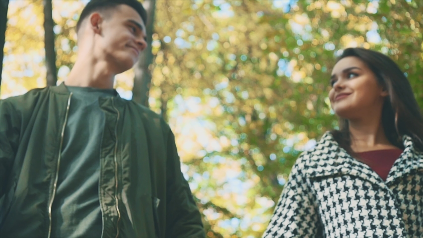 Slowmo. A loving couple walks in autumn park. They are smiling and talking. Blurred lower view. Copy space. 4K. | Shutterstock HD Video #1059135026