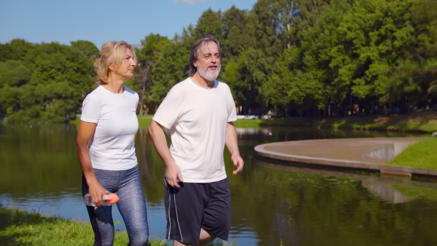 Happy caucasian old couple jogging running outdoors in park. Mature husband and wife doing cardio exercises running together by riverside in summer park Royalty-Free Stock Footage #1059142871