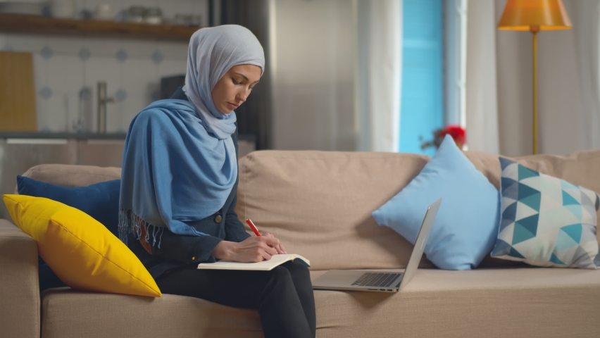 Smart attractive muslim businesswoman using laptop for working online writing schedule down sitting on couch at home. Young arab female in hijab studying online on computer Royalty-Free Stock Footage #1059142889