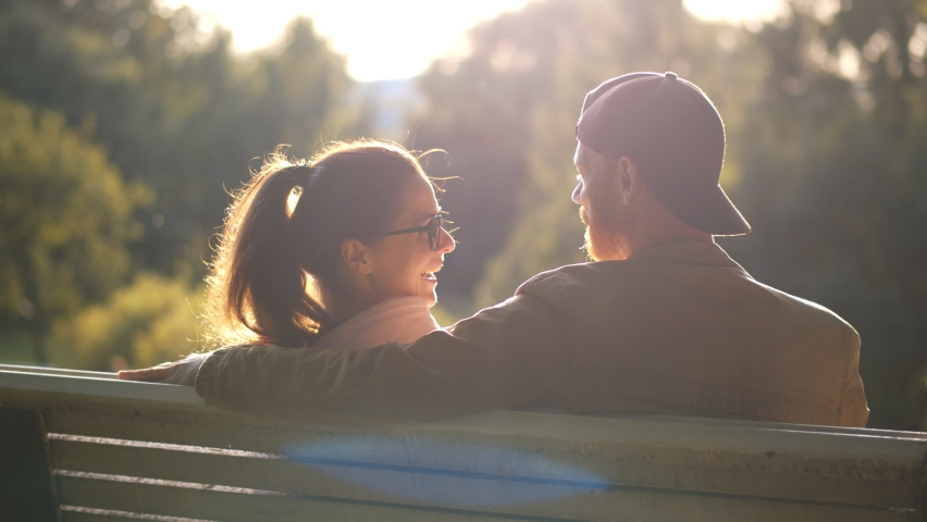 Back view of young loving couple having date on bench in park. Happy boyfriend and girlfriend enjoying time together hugging and relaxing on bench outdoors