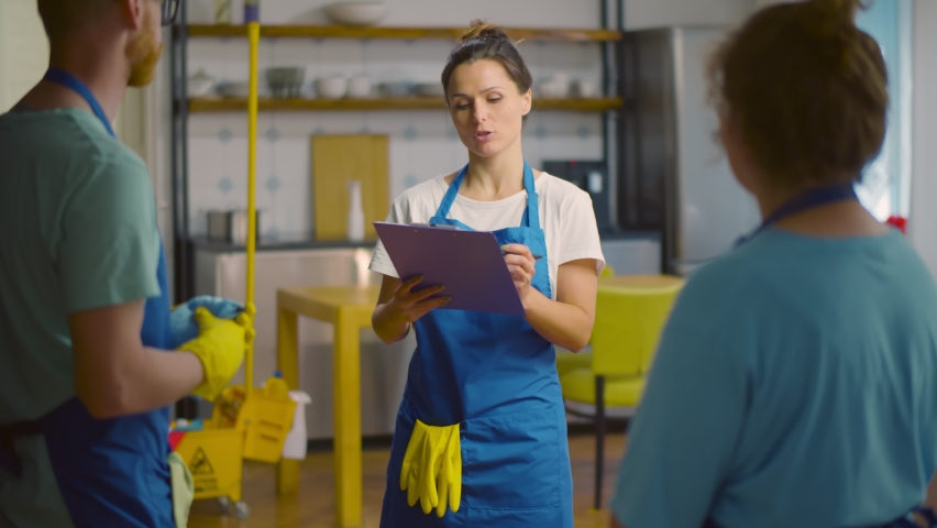 Team of janitors making check list in clipboard working in modern apartment. Cleaning service crew in uniform checking to-do list before leaving cleaned loft house | Shutterstock HD Video #1059142913