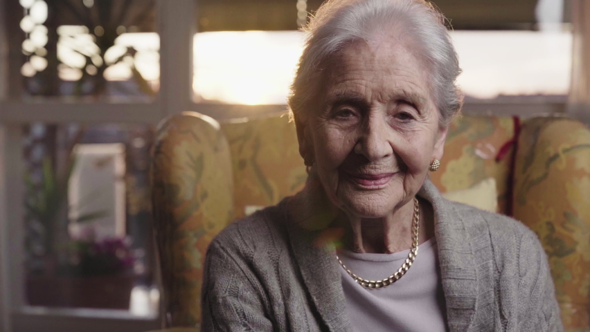 beautiful old lady portrait looking in camera with intense face sitting in the living room of her house in yellow armchair at golden hour, 90 years old healthy elderly woman. Slow motion parallax shot Royalty-Free Stock Footage #1059143906