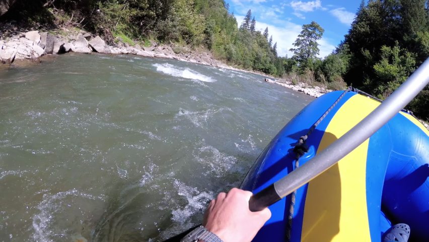 Rafting in the First Person on a Rough Mountain River. Extreme POV of the paddle and boat in motion. White Water Rafting on Rough Water. People Descending Raging Rapids from Whitewater. Chest View. | Shutterstock HD Video #1059144218