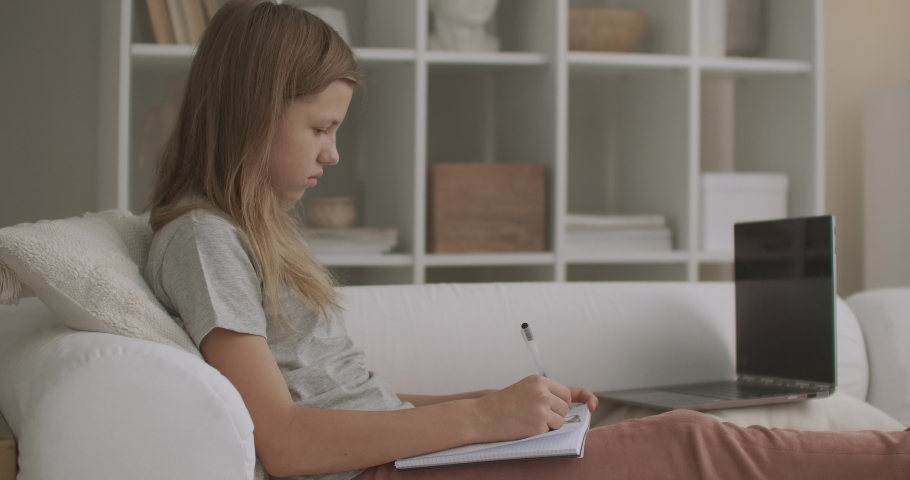 Teen girl is doing homework in room of flat after school, writing in exercise book, sitting on couch, e-learning for school children | Shutterstock HD Video #1059147953