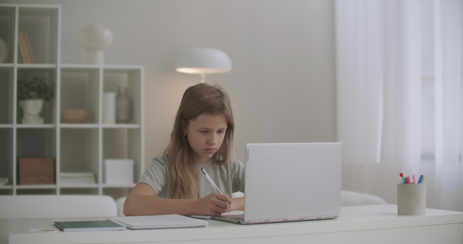 Schoolgirl is learning online at home, writing in copybook, doing dictation, listening teacher by laptop, distant education for schoolers | Shutterstock HD Video #1059147965