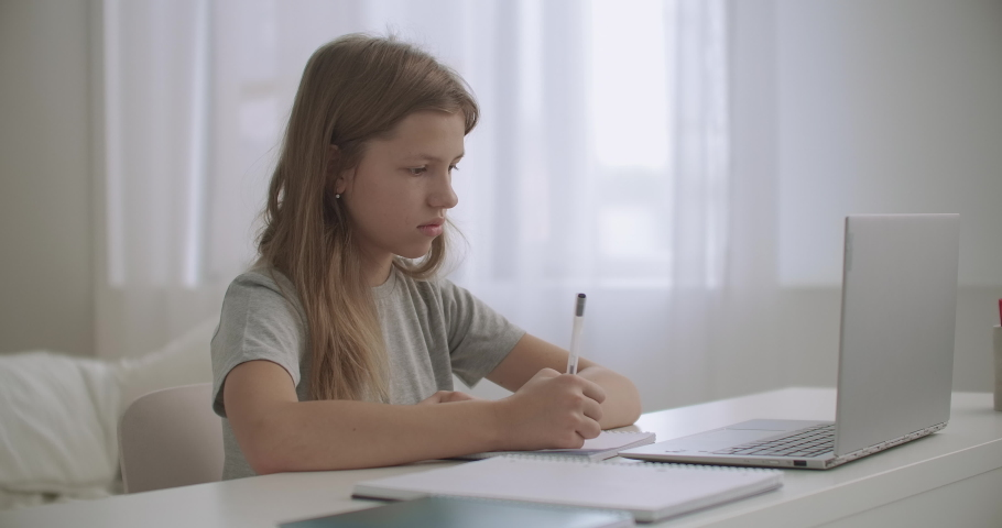 Teen girl is learning distantly at home, looking at screen of laptop and writing in exercise book | Shutterstock HD Video #1059148025