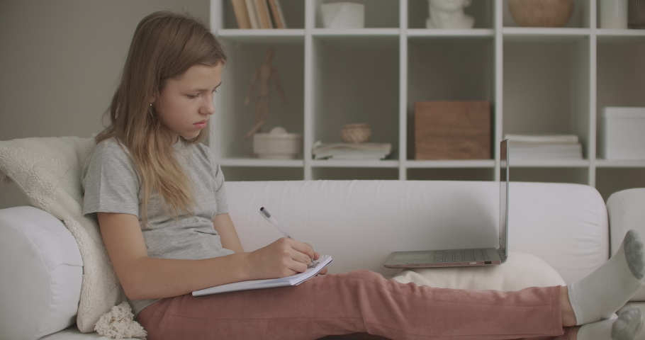 School girl is learning online, viewing lesson on display of laptop and doing exercises in copybook, sitting on couch at living room at daytime | Shutterstock HD Video #1059148037