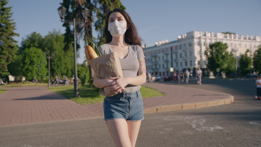 Young woman in protective mask and gloves carries bag with products from store to home. Pandemic shopping. Social distance for prevent outbreak. Another life after quarantine. Covid effect concept. | Shutterstock HD Video #1059151400