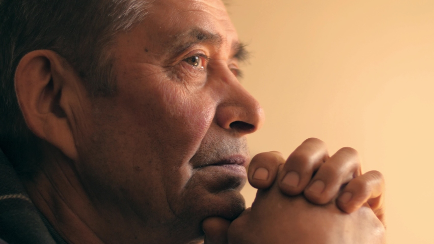 Senior man at home, looking up, praying prayer, thinking. Portrait, closeup, 4K UHD.