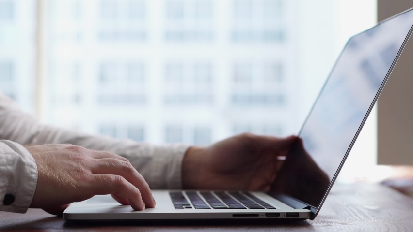 Close-up of hands of unrecognizable man turning off laptop and closing lid of computer at desk in modern office room on background of large window. Concept of completing work at computer. Royalty-Free Stock Footage #1059155276