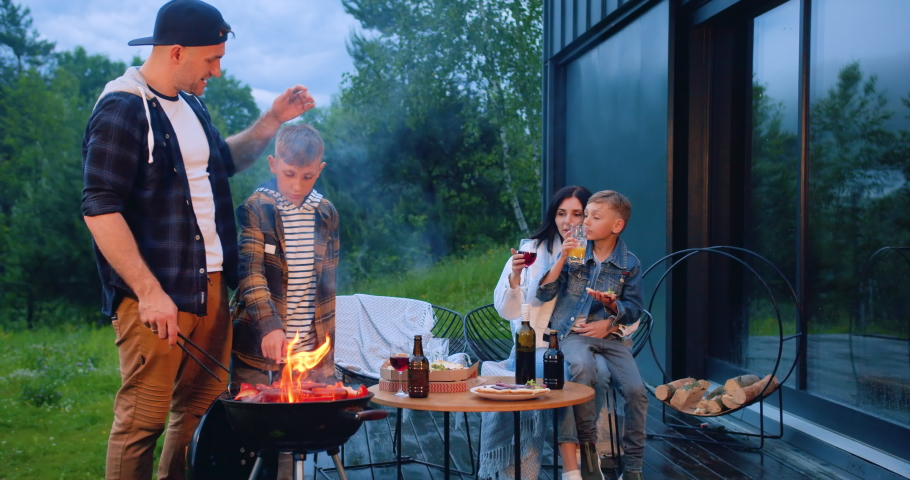 Portrait of attractive stylish cheerful loving family which having family barbecue celebration on the terrace near private modern house,slow motion