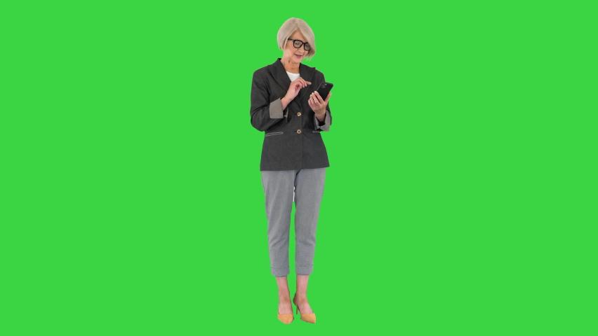 Elderly business woman works on a smartphone on a Green Screen, Chroma Key. | Shutterstock HD Video #1059160328