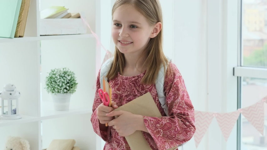 Cute little schoolgirl with backpack and supplies standing in light classroom | Shutterstock HD Video #1059162365