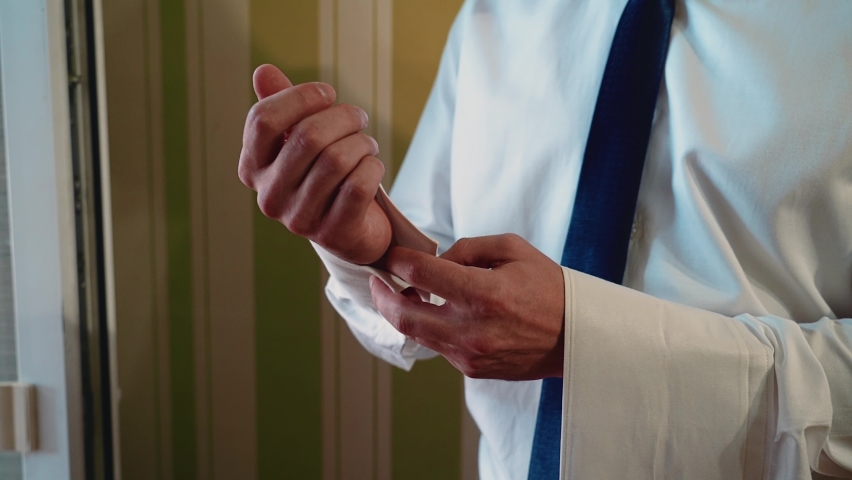 The man gets dressed. He buttons up the sleeves of his white shirt