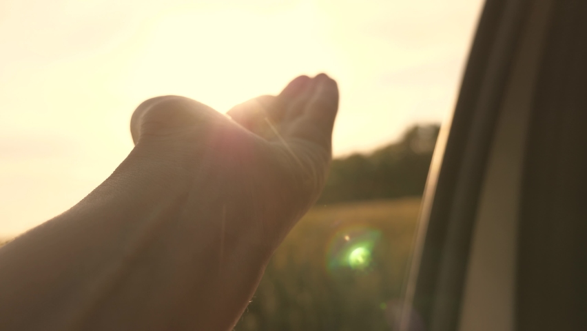 Girl sits in front seat of car, reaches out to window and catches glare of setting sun. travel and adventure concept. free woman travels by car catches sun and wind with her hand from car window.