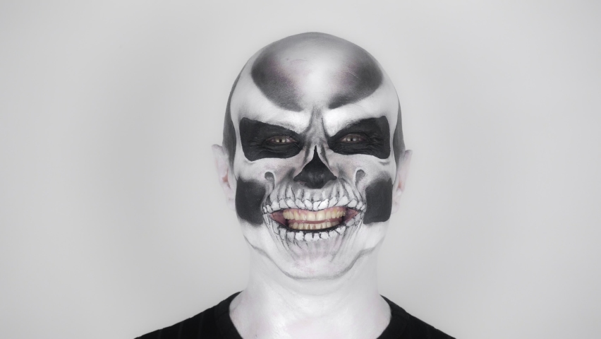 Cheerful funny man in skeleton make-up for Halloween smiles at the camera. Shooting in the studio. Gray background Royalty-Free Stock Footage #1059167246