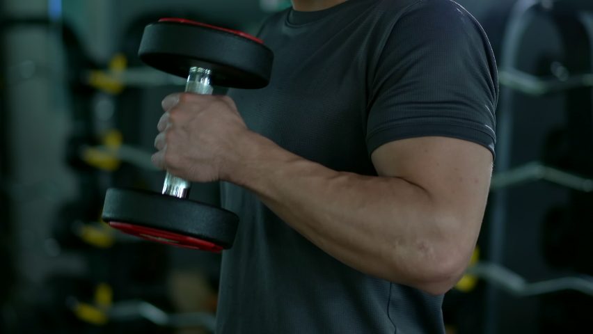 4K footage showing an unrecognizable people workout in the indoor gym, man lifting up a Hammer Curl weight exercise. Physical and muscle weight training  for body building workout. Royalty-Free Stock Footage #1059167603