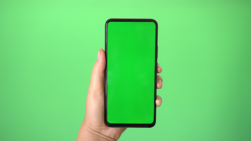 Woman's hand holding a mobile telephone with a vertical green screen in tram chroma key smartphone technology cell phone touch message | Shutterstock HD Video #1059168881