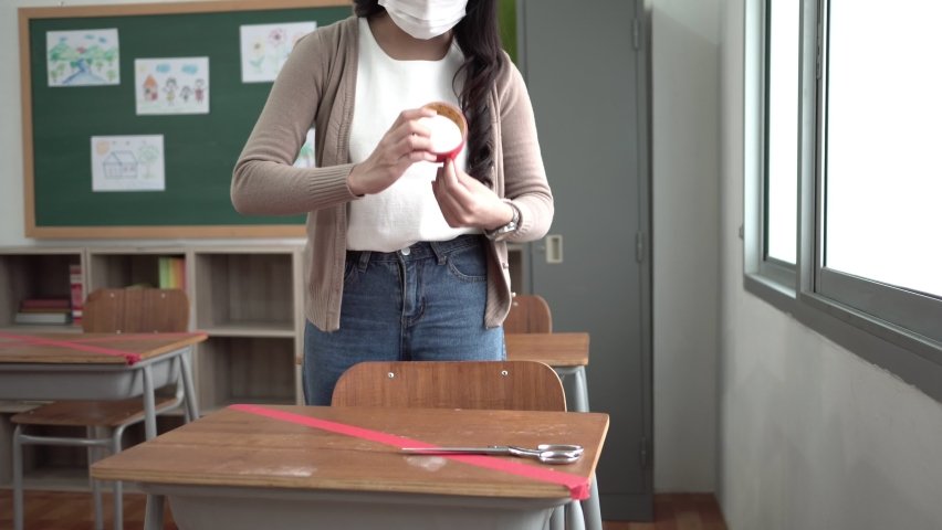 Asian Female Teacher applying marking red duct tape in crossed symbol on desk in classroom at school during coronavirus epidemic. Young Woman wearing protective face mask in social distancing concept | Shutterstock HD Video #1059169934