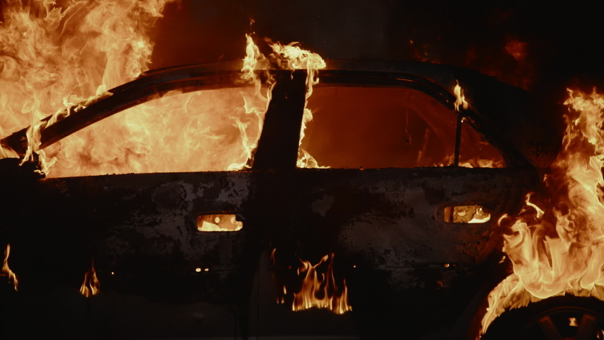Frame of a car burns brightly on fire at night