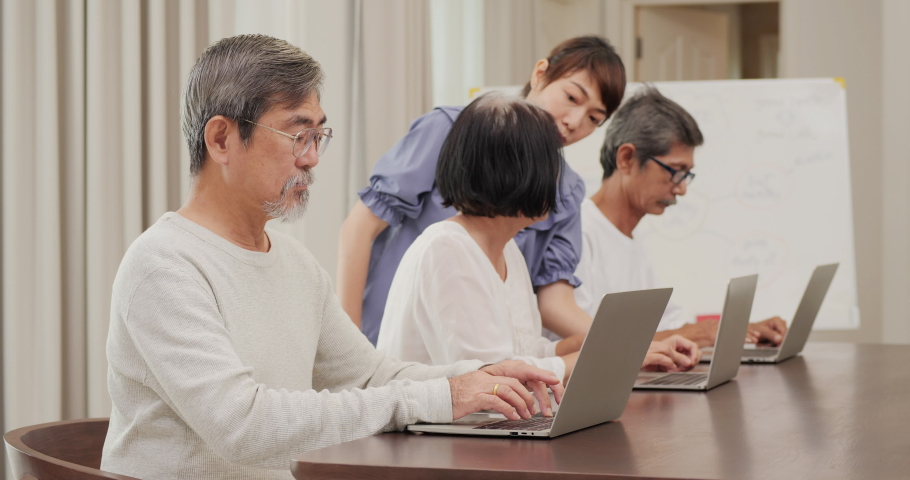 Senior man trying to learn how to use computer at classroom. Teacher take care of them to learn about modern technology. | Shutterstock HD Video #1059172157