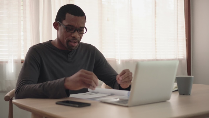 African American creative designer man making video call meeting and working on laptop at home. Black Freelancer male explaining discussing with business partner team or colleague or client  Royalty-Free Stock Footage #1059174134