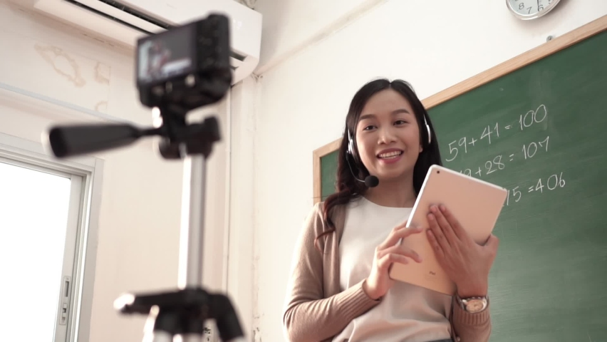 Female talking on video call with students, E-learning with internet wireless technology. Asian woman teacher standing online teaching with headphone and digital tablet in front of digital camera | Shutterstock HD Video #1059174140