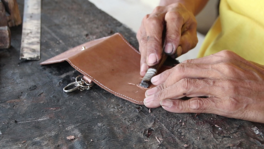 Blurry Selective focus clip, craftsman when carving leather for decoration, manually in his garage | Shutterstock HD Video #1059174809