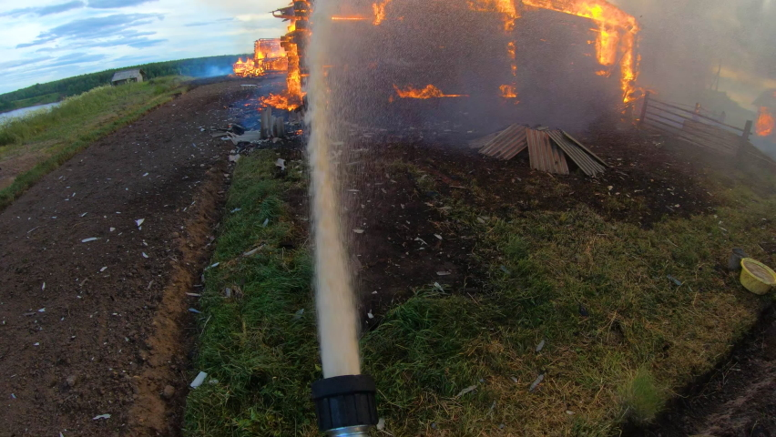 Massive fire in the village.Burning several houses at the same time.The fireman bravely extinguishes the fire with water.The plight of the people.Gopro. | Shutterstock HD Video #1059175871