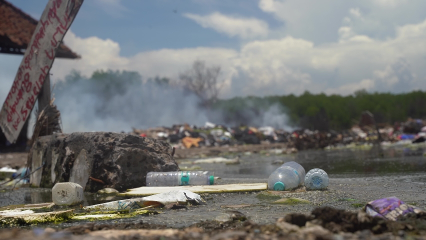 Burning trash and rubbish on beautiful beach during windy day. Smoke raises in the sky.Global pollution problem on Gili Island. | Shutterstock HD Video #1059178997
