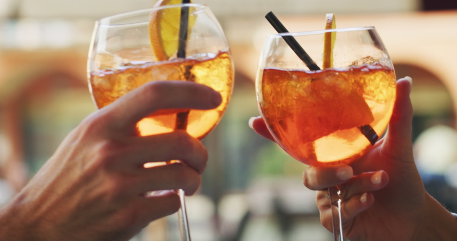 Close up shot of an young carefree romantic couple in love is drinking and cheering with cool alcohol cocktails while enjoying a happy hour time together in city center bar on a weekend in a sunny day. Royalty-Free Stock Footage #1059180083