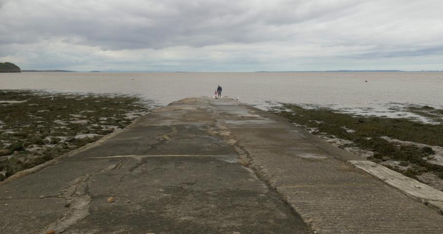 Grandparent and grandchild explore coastal slipway edge watching the sea on cloudy day, wide shot