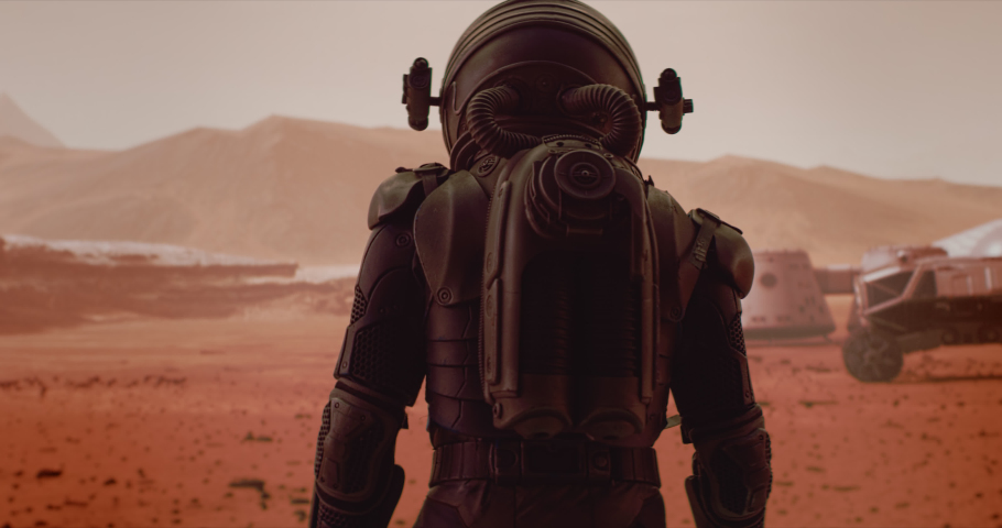 HANDHELD TRACKING back view of astronaut wearing space suit walking on a surface of a red planet. Martian base and rover in the background. Mars colonization concept | Shutterstock HD Video #1059183989