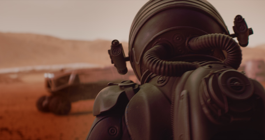 HANDHELD TRACKING back view of astronaut wearing space suit walking on a surface of a red planet. Martian base and rover in the background. Mars colonization concept | Shutterstock HD Video #1059187397