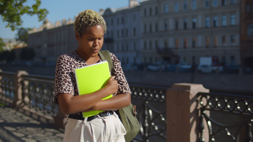 Portrait of sad african female student walking in street holding folders. Upset afro college woman walking by riverside in city anxious about problems in university or failed exams | Shutterstock HD Video #1059187892