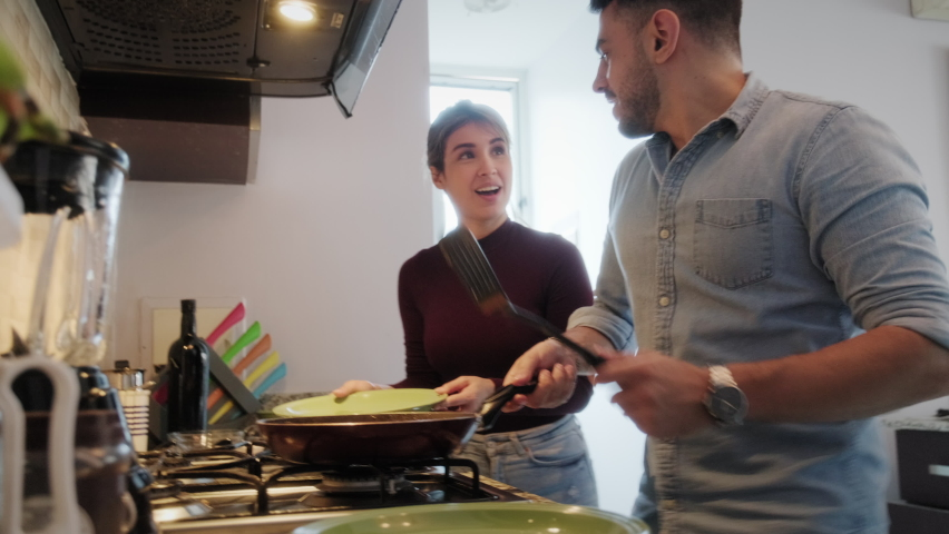 Young couple cooking food together at home with new recipe. Happy man and woman preparing omelette for lunch. Husband and wife smiling in kitchen. Married people and hobby