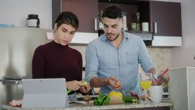 Young couple cooking food together at home, watching tutorial video for recipe on tablet. Happy man and woman preparing omelette. Husband and wife smiling in kitchen. Married partners and lifestyle
