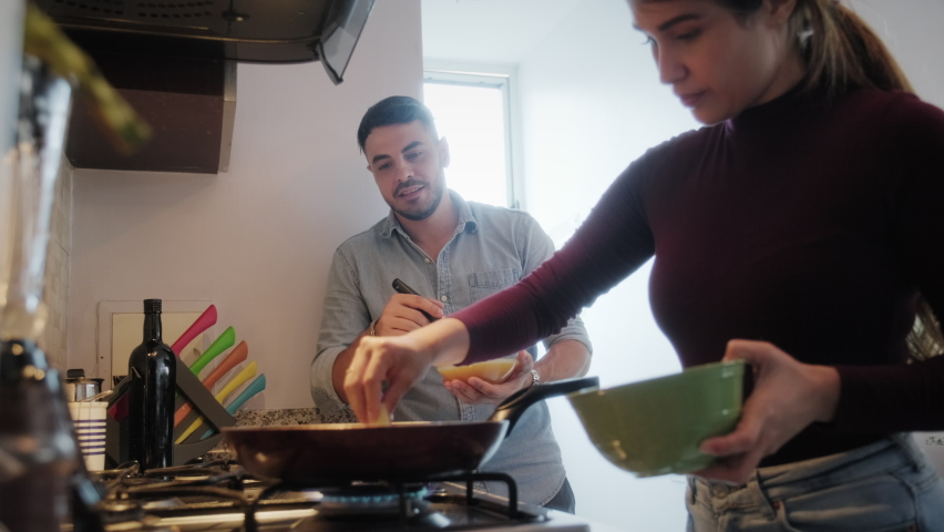 Young couple cooking food together at home with new recipe. Happy man and woman preparing omelette for lunch. Husband and wife smiling in kitchen. Married partners and lifestyle