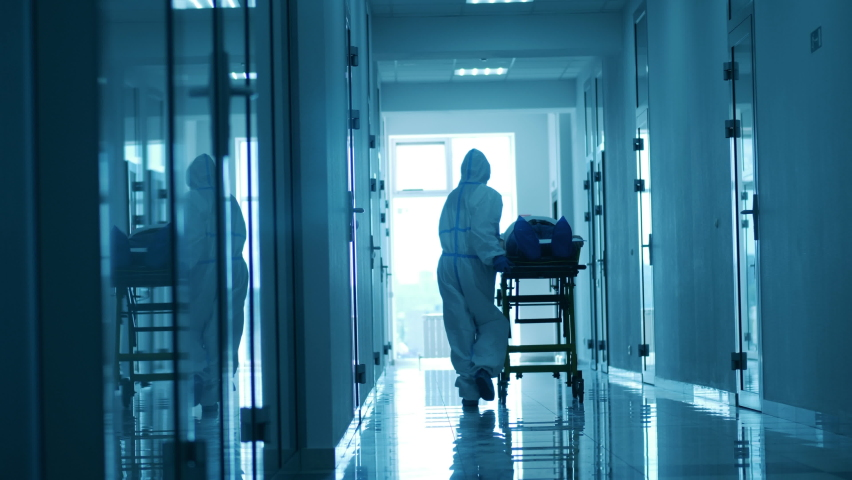 Doctor is moving a trolley with a patient along the hospital. Coronavirus hospital, COVID-19 clinic concept. Royalty-Free Stock Footage #1059188522