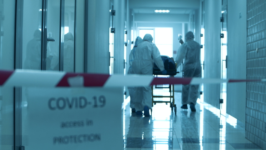 Doctors are taking a patient through a quarantined corridor. Coronavirus concept. Royalty-Free Stock Footage #1059188609